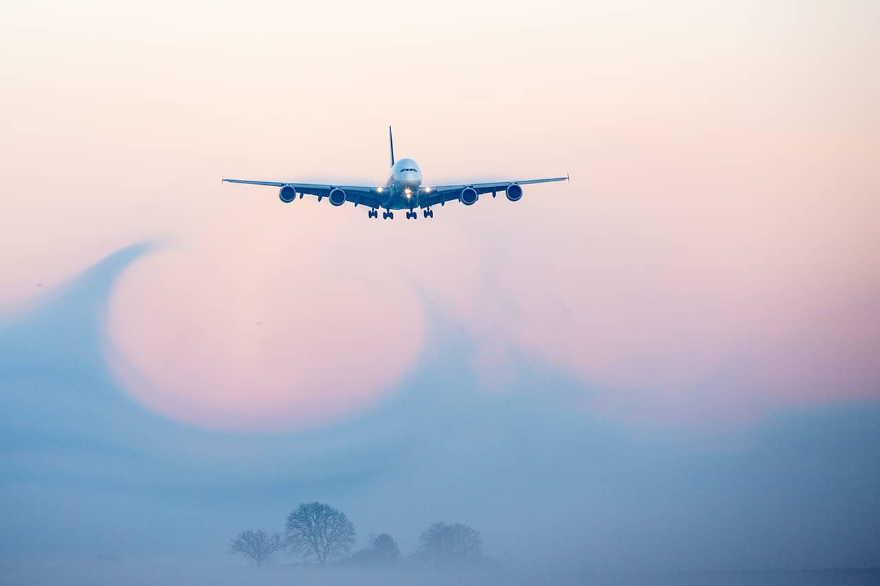 Aircraft producing CO2 emissions landing in low visibility conditions